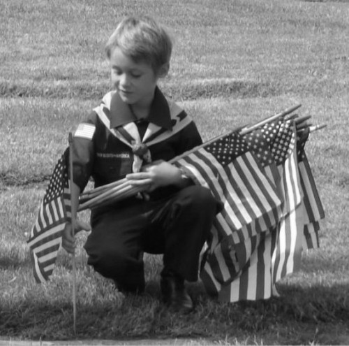 Boy scout Chas holding flags bw