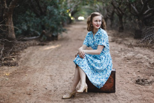 Lainey sitting on vintage suitcase