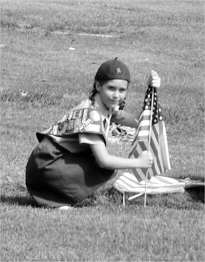 Girl Scout Brownie placing Flags on Veteran Grave